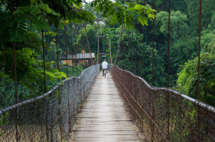 Man riding bicycle crosses the bridge in Battambang